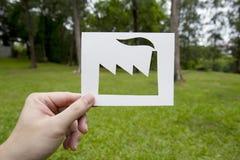 Έγγραφο εκμετάλλευσης χεριών που κόβεται στη μορφή εργοστασίων στην πράσινη χλόη Στοκ Φωτογραφίες