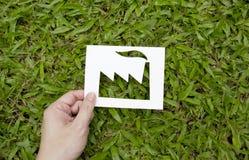 Έγγραφο εκμετάλλευσης χεριών που κόβεται στη μορφή εργοστασίων στην πράσινη χλόη Στοκ φωτογραφία με δικαίωμα ελεύθερης χρήσης