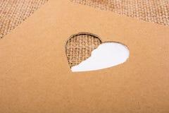 Έγγραφο και καμβάς που βλέπουν μέσω της μορφής καρδιών Στοκ εικόνα με δικαίωμα ελεύθερης χρήσης