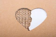 Έγγραφο και καμβάς που βλέπουν μέσω της μορφής καρδιών Στοκ Φωτογραφίες