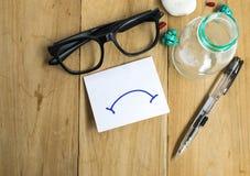 Έγγραφο με τα γυαλιά και τις μάνδρες στους ξύλινους πίνακες που χρησιμοποιούν την επιχείρηση για τη συγκίνηση σε κακό στοκ εικόνα