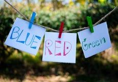 Έγγραφο με τα χρώματα λέξης γραφής, μπλε, κόκκινη, πράσινη ένωση για ένα σχοινί με τον ξύλινο συνδετήρα και αναπτυγμένος στον αέρ στοκ εικόνα