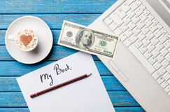 Έγγραφο, δολάριο, καφές και lap-top που βρίσκονται στον πίνακα Στοκ Φωτογραφία