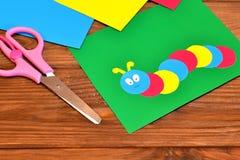 Έγγραφο παιδιών applique - χρωματισμένη κάμπια στο πράσινο φύλλο, φύλλο εγγράφου, ψαλίδι καφετής ξύλινος ανασκόπησης Στοκ φωτογραφία με δικαίωμα ελεύθερης χρήσης