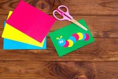 Έγγραφο παιδιών applique - χρωματισμένη κάμπια στο πράσινο φύλλο, φύλλο εγγράφου, ψαλίδι καφετής ξύλινος ανασκόπησης Στοκ Φωτογραφίες