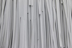 Έγγραφο που τεμαχίζεται στο άσπρο υπόβαθρο Ο καταστροφέας εγγράφων εγγράφου κρεμά στον άσπρο τοίχο Στοκ εικόνες με δικαίωμα ελεύθερης χρήσης