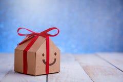 Έγγραφο σπιτιών με το περικάλυμμα χαμόγελου με τον κόκκινο δεσμό κορδελλών Στοκ Εικόνα