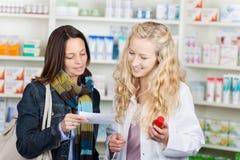 Έγγραφο συνταγών ανάγνωσης φαρμακοποιών και πελατών Στοκ Εικόνες
