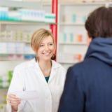 Έγγραφο συνταγών εκμετάλλευσης φαρμακοποιών εξετάζοντας τον πελάτη στοκ εικόνα με δικαίωμα ελεύθερης χρήσης