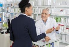 Έγγραφο συνταγών εκμετάλλευσης φαρμακοποιών εξετάζοντας Businesswoma στοκ εικόνες