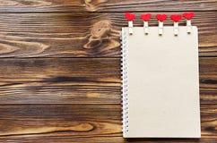 Έγγραφο της Kraft notepade με τα μικρά clothespins με τις καρδιές στο woode στοκ εικόνα με δικαίωμα ελεύθερης χρήσης