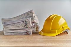 Έγγραφο υπερφόρτωσης σωρών της έκθεσης με το κίτρινο καπέλο μηχανικών στοκ φωτογραφία