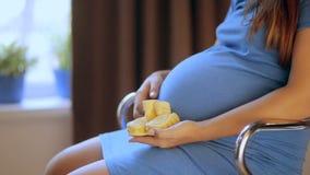 Έγκυα ευτυχή παπούτσια μωρών εκμετάλλευσης γυναικών στα χέρια της Mom που αναμένει το μωρό της έγκυος γυναίκα κοιλιών Εγκυμοσύνη  φιλμ μικρού μήκους