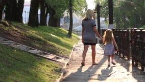 Έγκυες μητέρα και αυτή λίγος ευτυχής περίπατος κορών στο ηλιόλουστο πάρκο, πίσω άποψη απόθεμα βίντεο