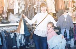 Έγκυες μητέρα και κόρη που επιλέγουν romper το κοστούμι για το μωρό στο CH Στοκ Εικόνες