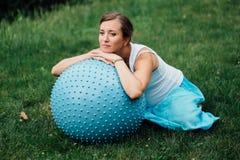 Έγκυες προγενέθλιες να κάνει γιόγκας διαφορετικές ασκήσεις με το fitball στο πάρκο στη χλόη, αναπνοή, τέντωμα, Pilates Στοκ Εικόνα