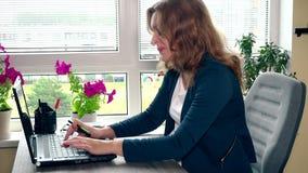 Έγκυες σημειώσεις γραψίματος επιχειρηματιών Έγκυος ώριμη γυναίκα που εργάζεται στο γραφείο φιλμ μικρού μήκους