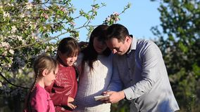 Έγκυοι mom, μπαμπάς και κόρη που παίρνουν τις εικόνες μου με το τηλέφωνο στο ανθισμένο πάρκο, τη μητέρα και τα παιδιά άνοιξη απόθεμα βίντεο