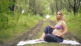 Έγκυος γιόγκα στη θέση λωτού στο πάρκο στη χλόη στο χαλί, που κάνει τις ασκήσεις, αναπνοή, τέντωμα απόθεμα βίντεο