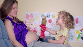 Έγκυος γυναίκα και η κόρη της με παιγνίδια γάτα που φιλιέται με κοιλιά της μητέρας απόθεμα βίντεο