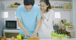 Έγκυος γυναίκα και ο σύζυγός της που προετοιμάζουν τα υγιή τρόφιμα μαζί στην κουζίνα στο σπίτι απόθεμα βίντεο