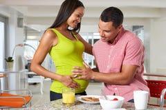 Έγκυος γυναίκα και σύζυγος που έχουν το πρόγευμα στην κουζίνα στοκ φωτογραφία με δικαίωμα ελεύθερης χρήσης