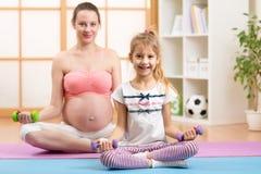 Έγκυος γυναίκα και το παλαιότερο παιδί της που κάνουν την ικανότητα Στοκ Εικόνες