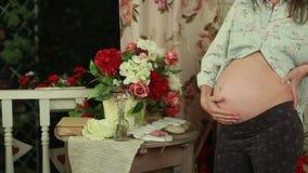 Έγκυος γυναίκα κοντά στον πίνακα με το ντεκόρ φιλμ μικρού μήκους