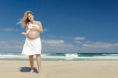 Έγκυος γυναίκα με ένα χαμόγελο στην κοιλιά στοκ εικόνα