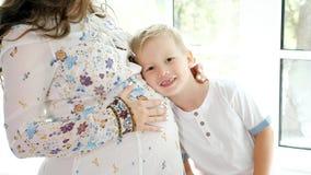 Έγκυος γυναίκα με λίγο γιο στη στρωματοειδή φλέβα παραθύρων στοκ φωτογραφία
