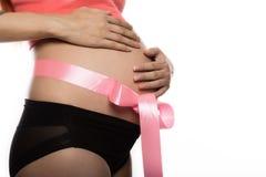 Έγκυος γυναίκα με μια ρόδινη κορδέλλα στην κοιλιά της κίνηση αργή στοκ φωτογραφία με δικαίωμα ελεύθερης χρήσης
