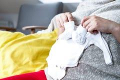 Έγκυος γυναίκα με τα ενδύματα μωρών Στοκ εικόνες με δικαίωμα ελεύθερης χρήσης
