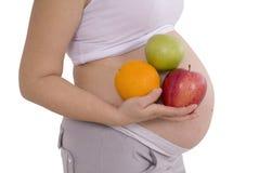 Έγκυος γυναίκα με τα φρούτα που ψαλιδίζει την πορεία Στοκ Φωτογραφίες