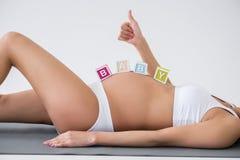 Έγκυος γυναίκα με τη λέξη μωρών Στοκ Εικόνες