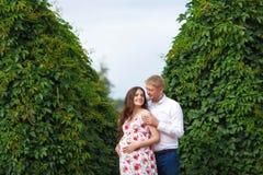 Έγκυος γυναίκα με το περπάτημα συζύγων στο πάρκο Στοκ Φωτογραφίες