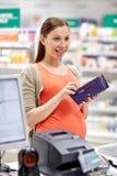 Έγκυος γυναίκα με το πορτοφόλι στο ταμείο στο φαρμακείο στοκ φωτογραφία με δικαίωμα ελεύθερης χρήσης