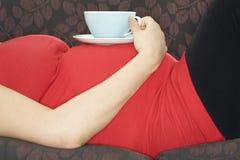 Έγκυος γυναίκα με το ποτό που βρίσκεται στον καναπέ Στοκ Φωτογραφίες