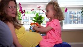 Έγκυος γυναίκα μητέρων και καλό παιχνίδι κοριτσιών κορών με το ρολόι παιχνιδιών στο στομάχι απόθεμα βίντεο