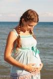 Έγκυος γυναίκα που αγκαλιάζει την κοιλιά στην παραλία Στοκ Φωτογραφίες