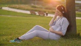 Έγκυος γυναίκα που ακούει τη μουσική στο ηλιοβασίλεμα απόθεμα βίντεο