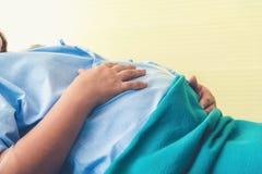 Έγκυος γυναίκα που βρίσκεται στην αναμονή κρεβατιών για να γεννήσει σε ένα νοσοκομείο στοκ φωτογραφίες