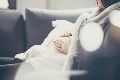 Έγκυος γυναίκα που βρίσκεται στον καναπέ και που αγκαλιάζει την κοιλιά της Φωτογραφία με το s Στοκ Εικόνες