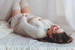 Έγκυος γυναίκα που βρίσκεται στο κρεβάτι στην κρεβατοκάμαρα Πυροβολισμός κινηματογραφήσεων σε πρώτο πλάνο στοκ εικόνες