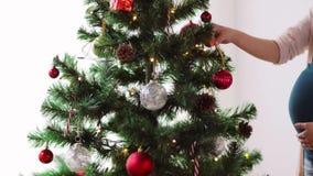 Έγκυος γυναίκα που διακοσμεί το χριστουγεννιάτικο δέντρο στο σπίτι φιλμ μικρού μήκους