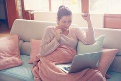 Έγκυος γυναίκα που εργάζεται σε έναν καναπέ Στοκ Φωτογραφίες