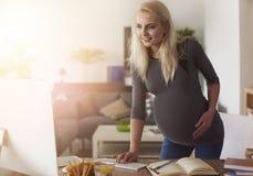 Έγκυος γυναίκα που εργάζεται στο σπίτι στοκ φωτογραφίες