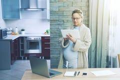 Έγκυος γυναίκα που εργάζεται ως freelancer με την ταμπλέτα Στοκ Εικόνες