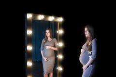 Έγκυος γυναίκα που θαυμάζει τη μορφή της σε έναν καθρέφτη στοκ φωτογραφία με δικαίωμα ελεύθερης χρήσης