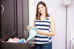 Έγκυος γυναίκα που διπλώνει τα ενδύματα μωρών στοκ φωτογραφία με δικαίωμα ελεύθερης χρήσης