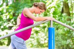 Έγκυος γυναίκα που κάνει τις ασκήσεις εγκυμοσύνης στο ικανότητα-ίχνος στοκ φωτογραφία